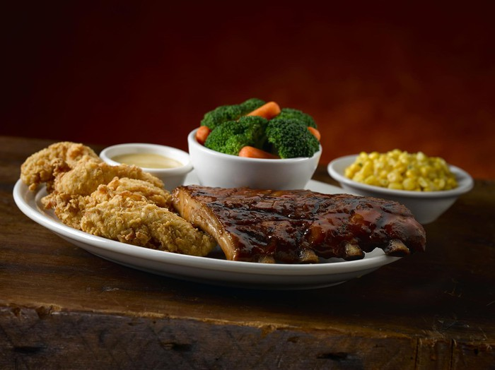 A plate with steak, fried chicken, and vegetables from Texas Roadhouse.