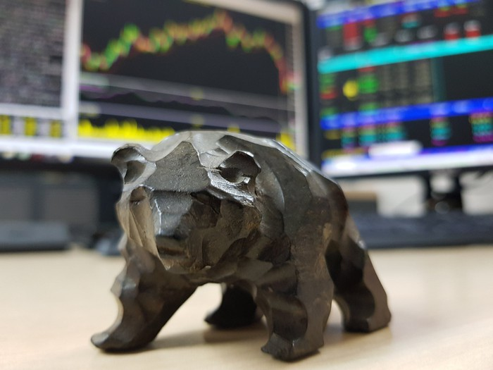 A bear figurine placed in front of trading screens.