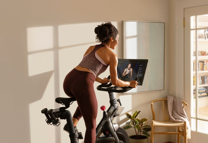A woman riding a Peloton connected bike in her home