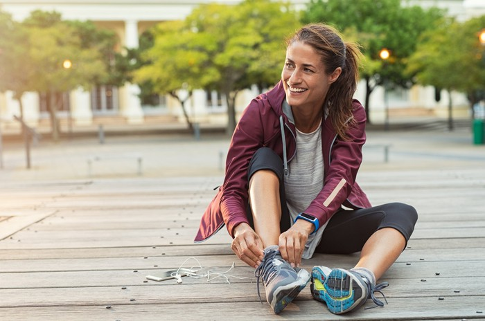 A smiling woman sitting outside while putting on sneakers.