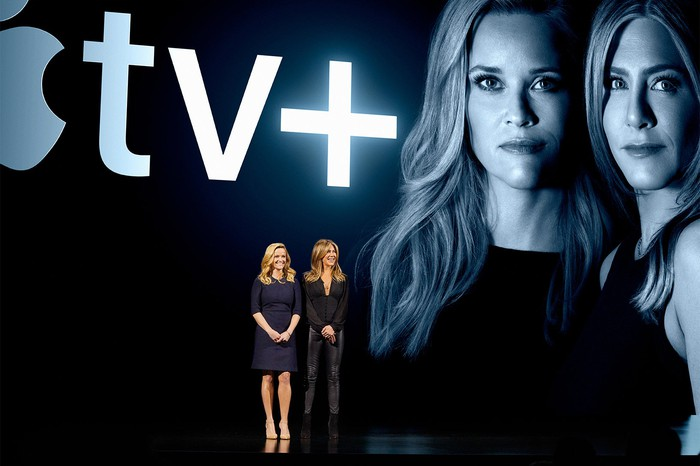 Reese Witherspoon and Jennifer Aniston on stage with the Apple TV+ logo and their photo projected on a screen behind them