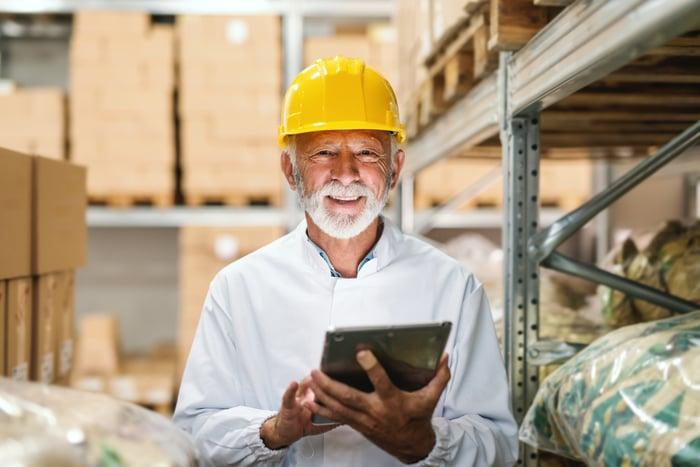 Smiling older man wearing yellow hard hat in warehouse