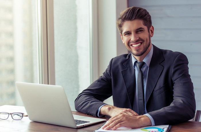 Smiling man in business suit and tie at laptop