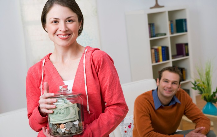 Smiling woman standing up holding glass jar of bills and coins while seated smiling man looks on