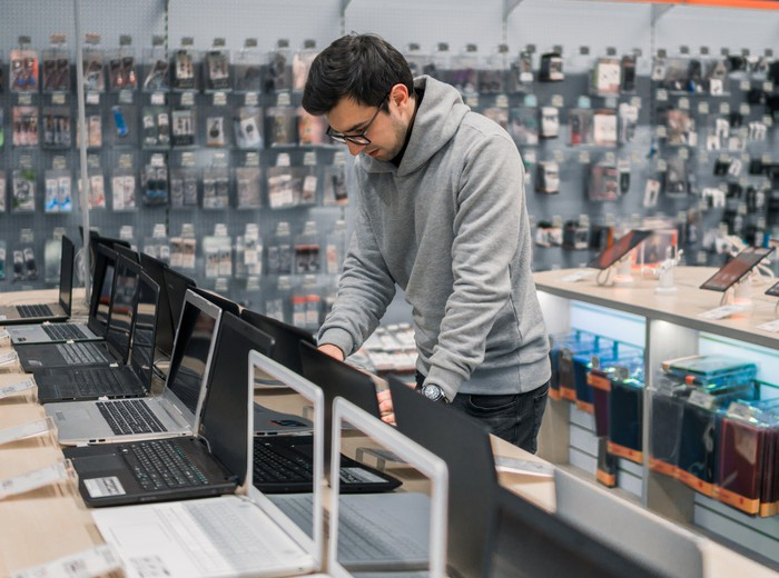 A man in an electronics store shopping for a laptop