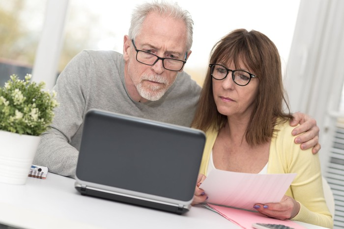 An older couple with concerned expressions sit at a table and look at a laptop screen.