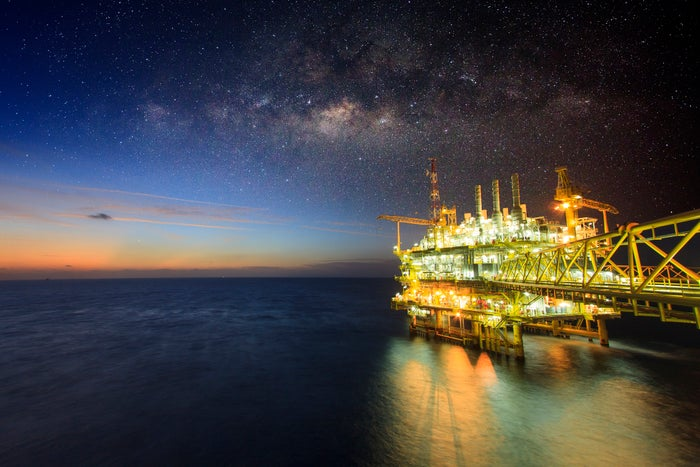 An offshore oil rig lit up at night