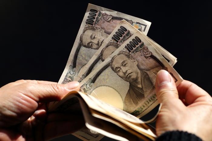 Close-up of someone fingering through Chinese Yuan bills.