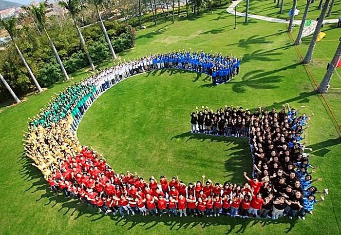 People in various colored shirts stand in the shape of Google's G logo