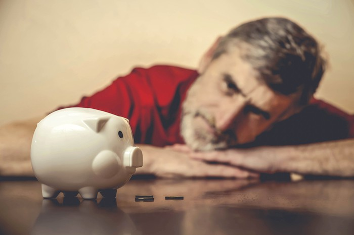 A dejected mature man staring at a piggy bank while laying his head on his hands.