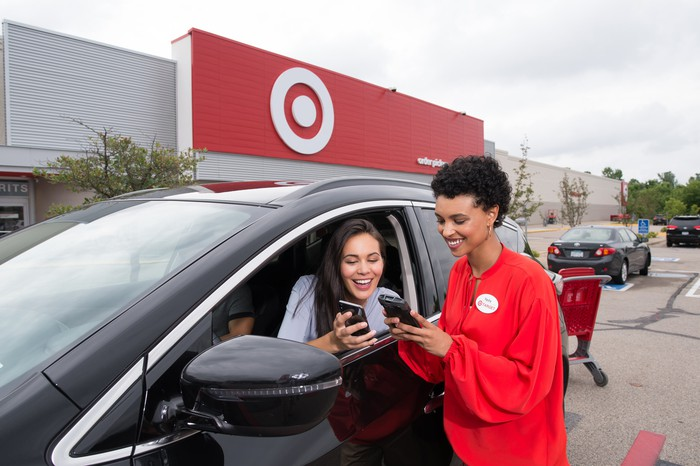 A customer sitting in her car in a Target parking lot chats with a Target employee standing at her window