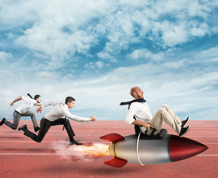 Three men racing in business attire with one tied to a rocket
