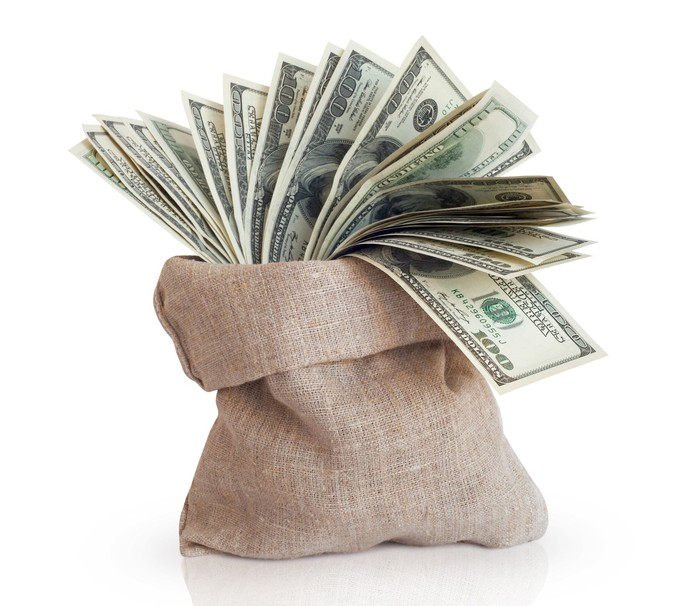 A burlap bag filled with cash peeking out of it.