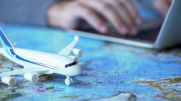 A model airplane sits on a map while a person types on a laptop in the background.