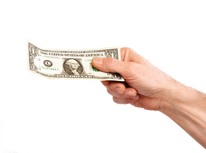 A hand holding a one dollar bill.