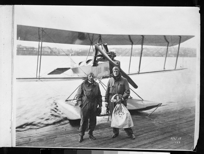 Two men pose in front of a Model C seaplane.