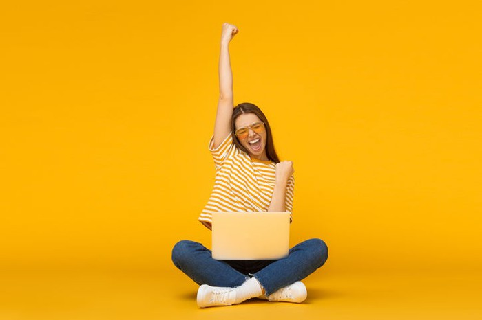 An excited woman, in a yellow shirt and in front of a yellow background, with her arm raised in the air as she checks her yellow laptop.