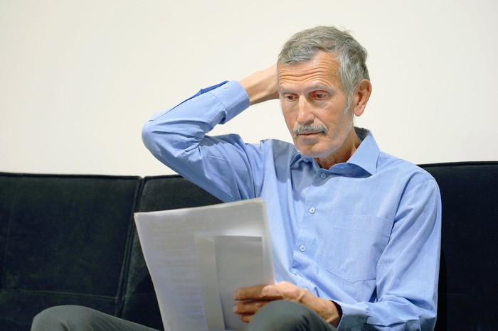Older man sitting on a couch, looking at a document, and scratching his head.
