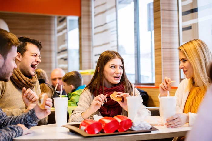 Two men and two women eating at a table inside a fast-food restaurant