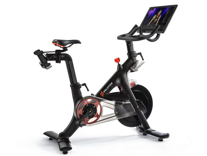 Stationary bike with Peloton logo, along with display showing exercise program.