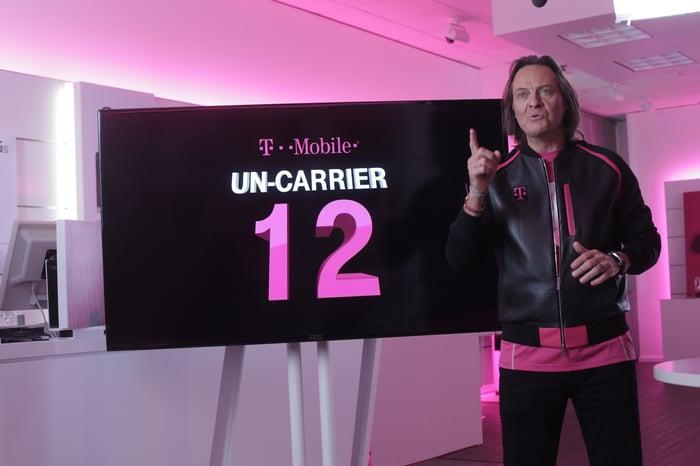 "John Legere in front of an ""Un-carrier 12"" sign"