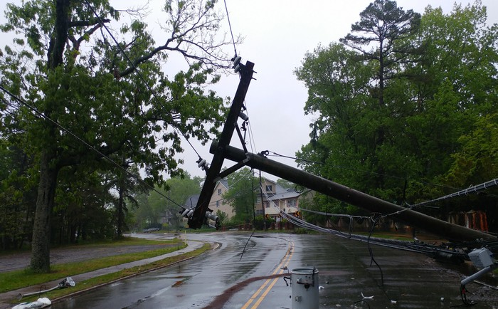 A pole bearing electric lines, toppled across a tree-lined residential street