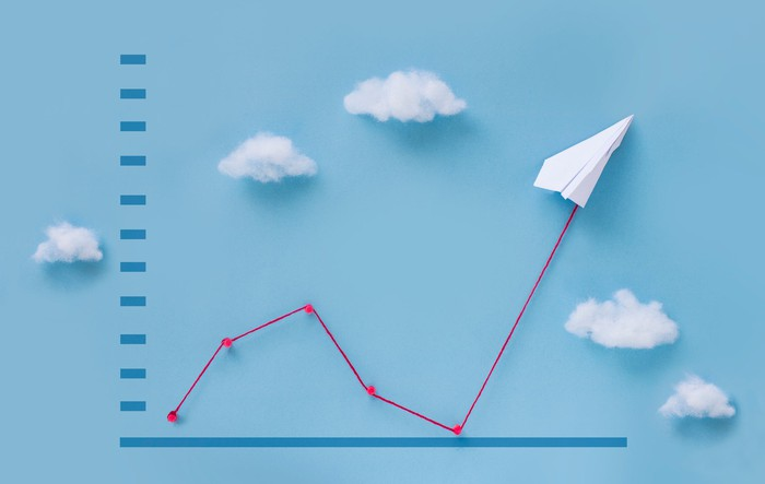 A chart showing a red line bouncing higher, headed by a paper airplane flying through the clouds.
