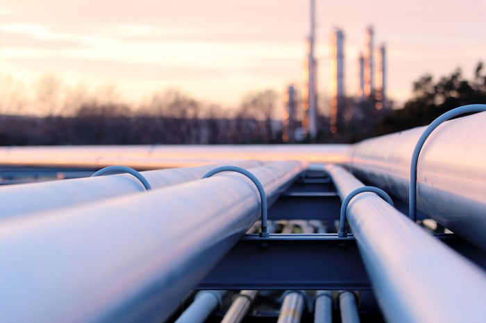 A closeup of pipelines with a gas plant in the background