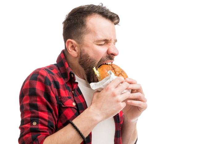 A man taking a big bite of a burger