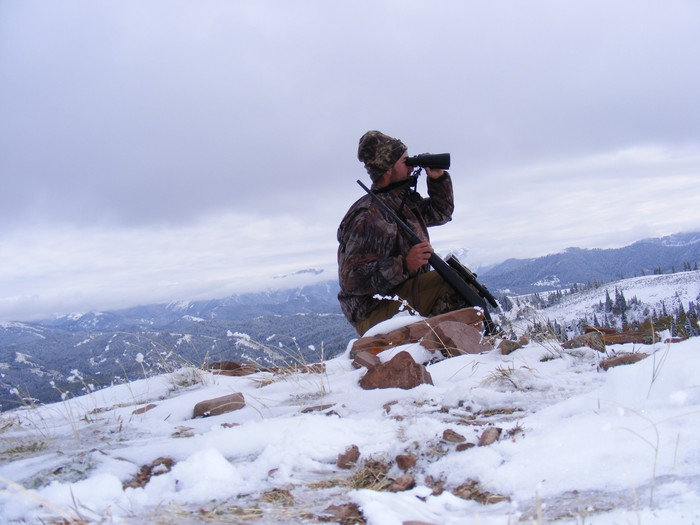 Man hunting on mountainside in winter.