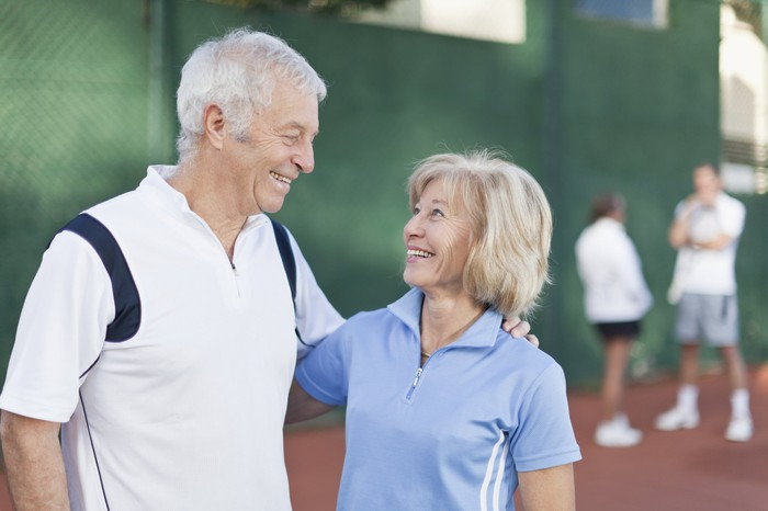 Smiling older man and woman in tennis outfits putting arms around each other