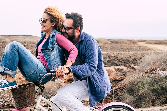 Man riding a bike while a smiling woman sits on its handlebars