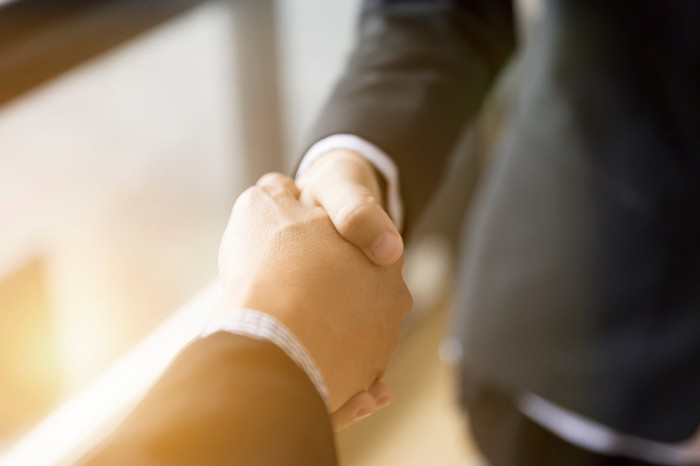 Arms in business suits shaking hands