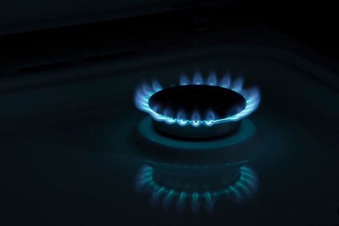 A gas burner emits blue flames