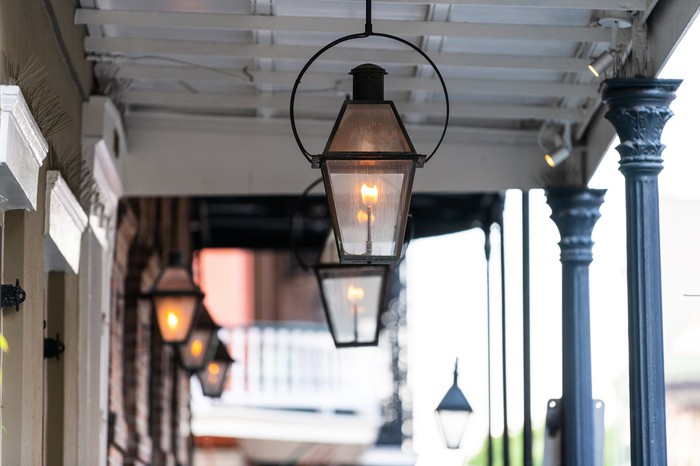 Gas lamps hang on an antique porch