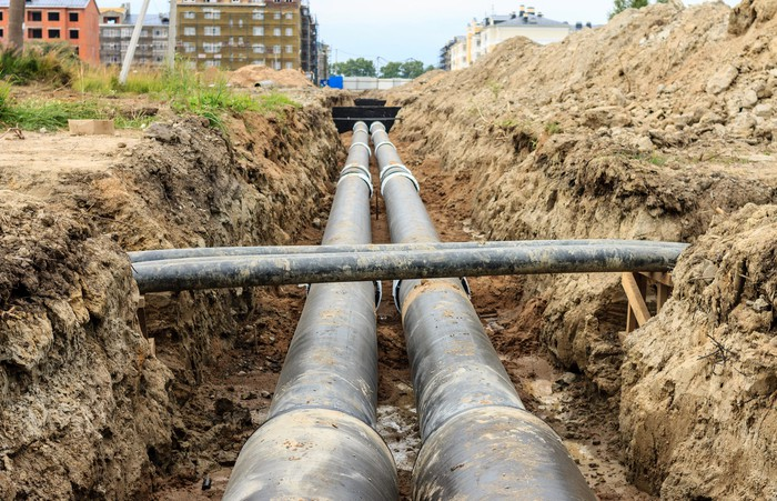 A pair of large pipes in a trench.