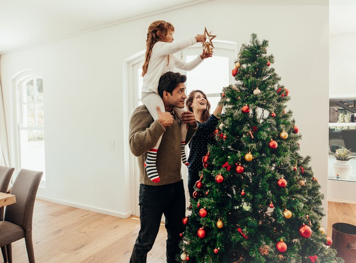 Man lifts girl on his shouldes to place star on Christmas tree while woman looks on