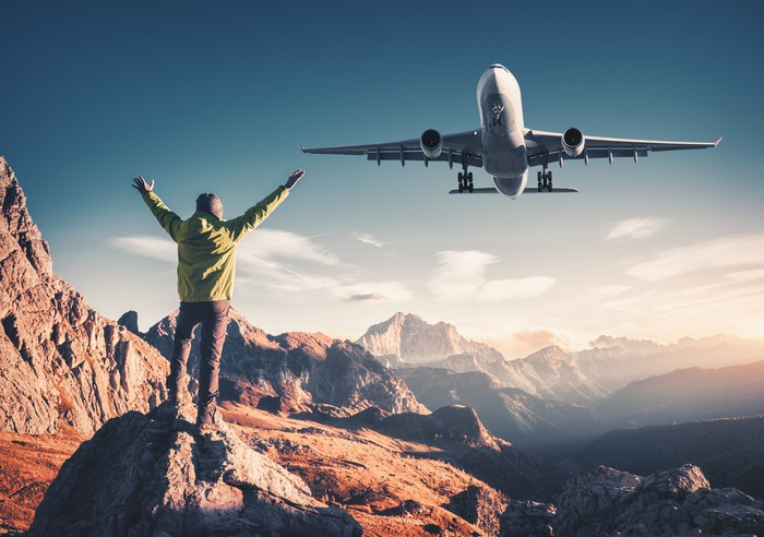Man surrounded by mountains raising his arms while a plane flies overhead.