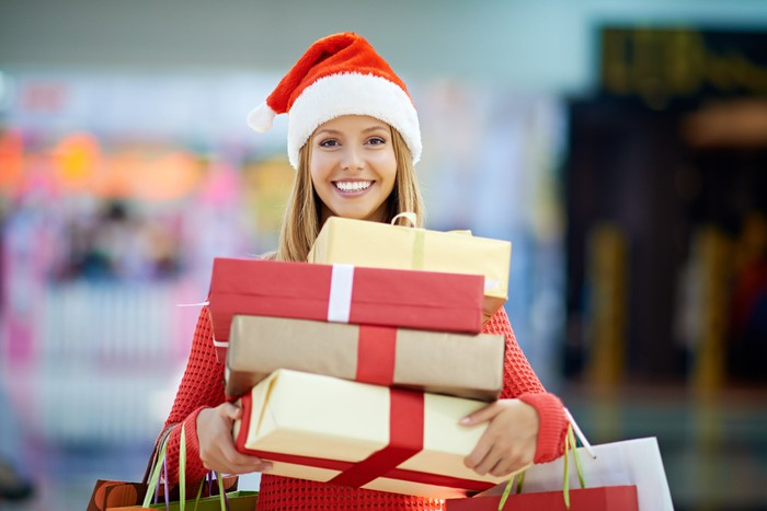 Smiling woman in a Santa hat, holding gift packages