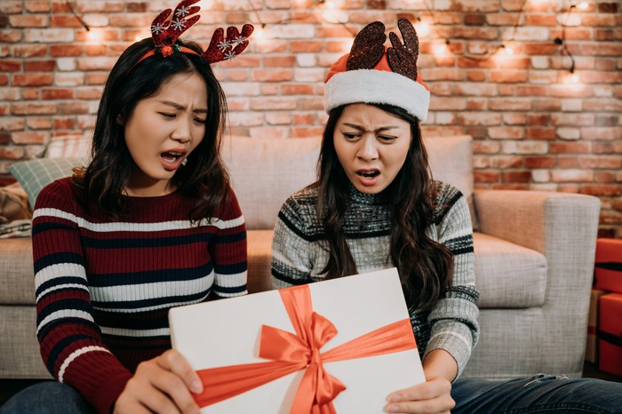 Two people look shocked opening a present.