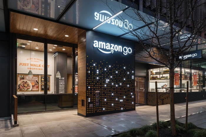 The exterior of an Amazon Go store lit up at night.