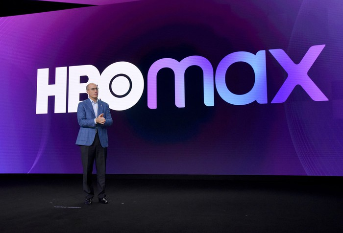 John Stankey standing on a stage in front of the HBO Max logo