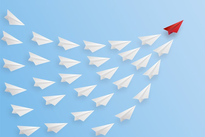 A cluster of white paper airplanes ascending as a red paper airplane leads the pack.