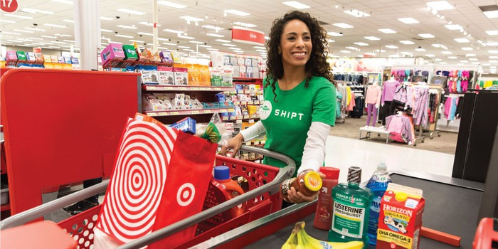 A Target Shipt employee going through a checkout line with a digital order for delivery.