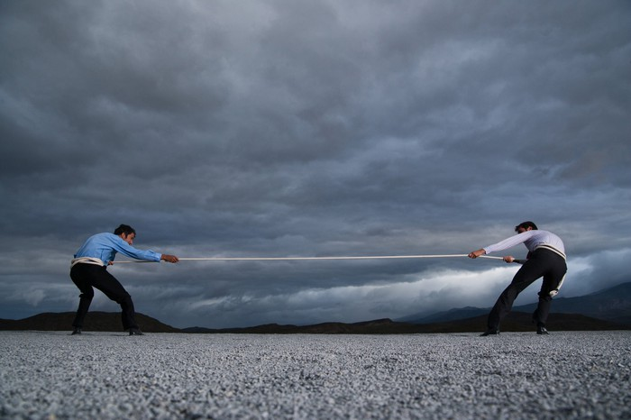 Two men pulling on opposite sides of rope in front of a dramatic landscape