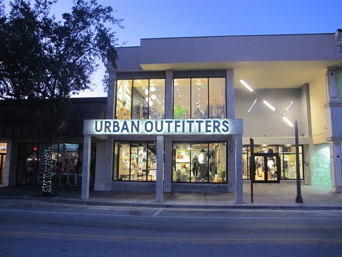 Front of Urban Outfitters location as seen from across a street at dusk.