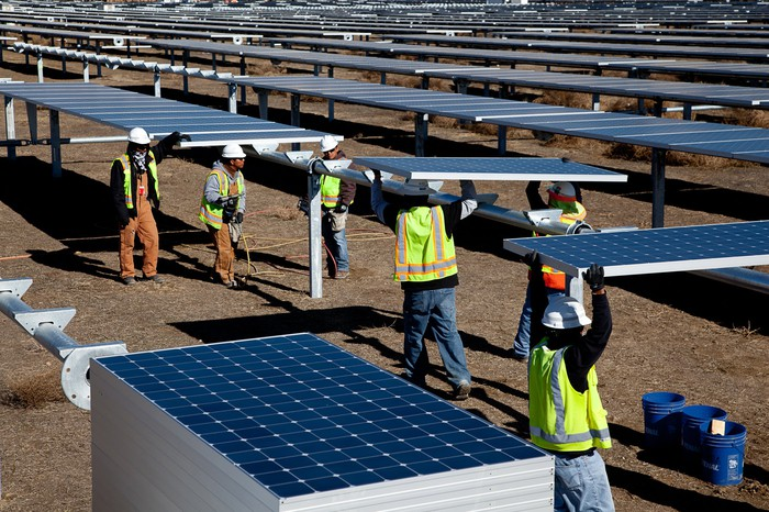 Workers installing solar panels at solar farm.