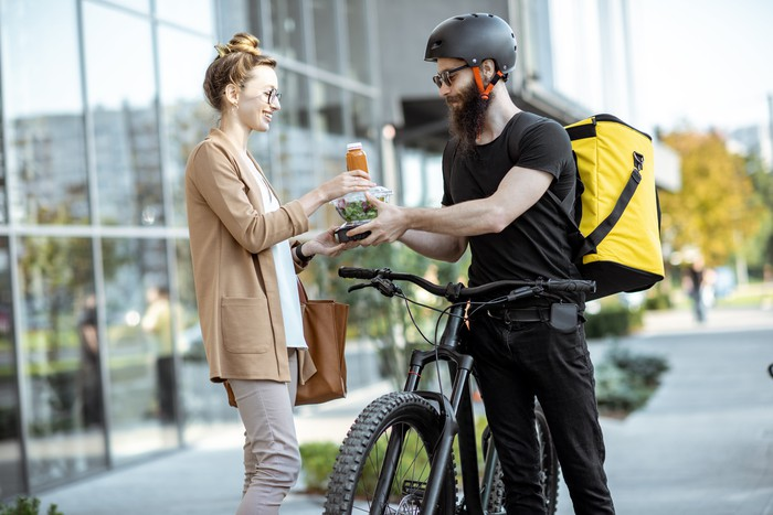 A food delivery person on a bike giving a salad and beverage to a woman