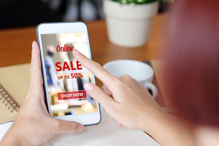 Picture of woman holding a smartphone, looking at an advertisment for a sale.