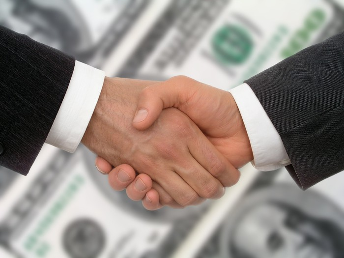 Two men shaking hands, with hundred dollar bills in the background.